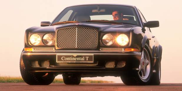 Low, front view of a black Continental T parked on a field road | Bentley Motors