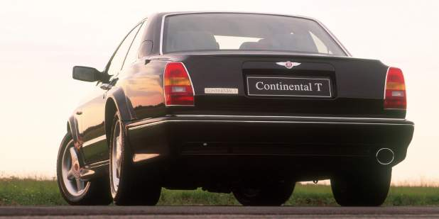 Low, rear view of a black Continental T parked in a field | Bentley Motors