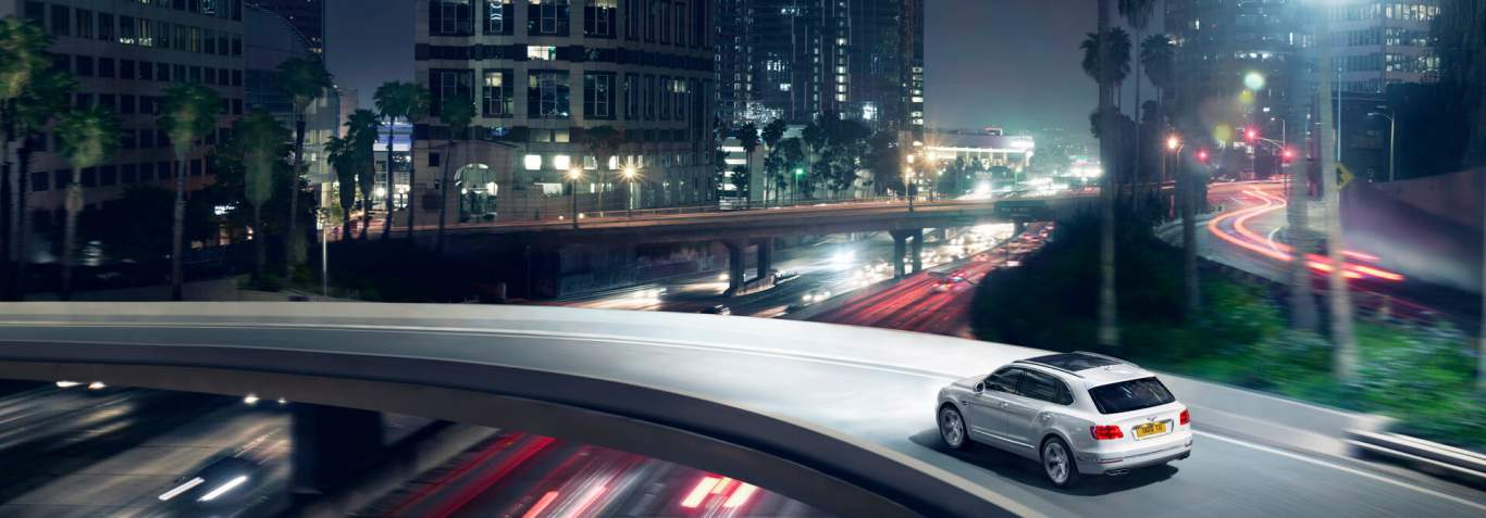 Bentayga Hybrid driving on city overpass at night with buildings in background 1920x670.jpg