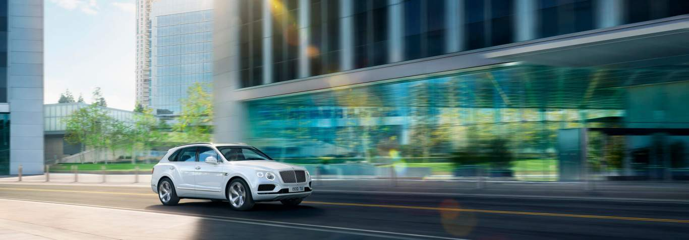 Bentayga-Hybrid-in-white-colour-driving-with-building-on-right-through-city