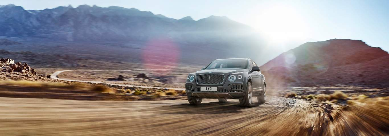 Grey Bentayga Driving Off Road With The Sun King Through Mountain View Bentley Motors