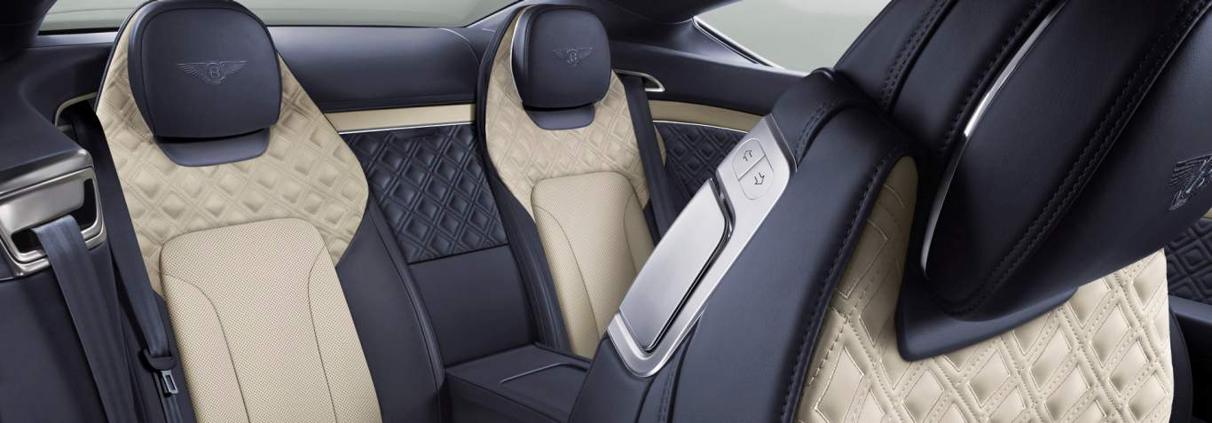 New Bentley Continental GT interior showing rear seats in blue and off white quilted leather with front seat tilted forward