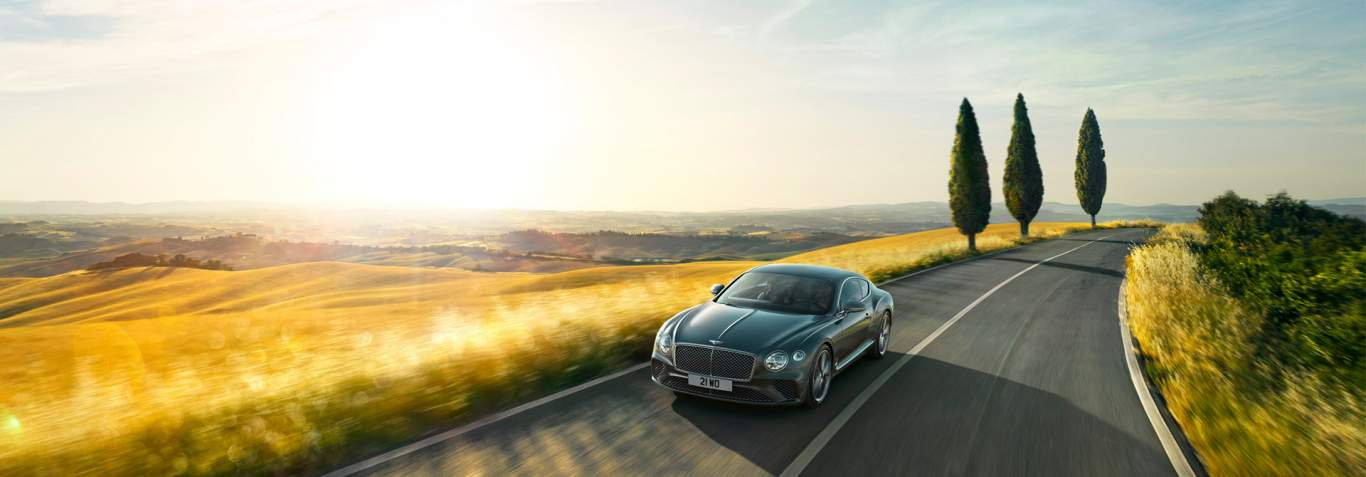 New Continental GT 2017 in Tungsten metallic grey paint driving past a golden field in Italy