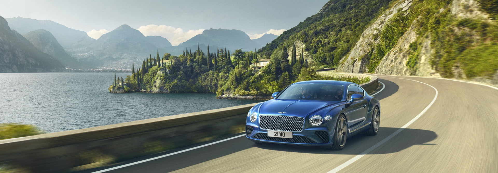 New Bentley Continental GT 2017 in Sequin Blue colour driving by an Italian lake in the sunshine