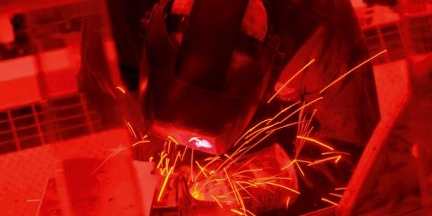 Red coloured image of a Bentley engineer welding metal | Bentley Motors