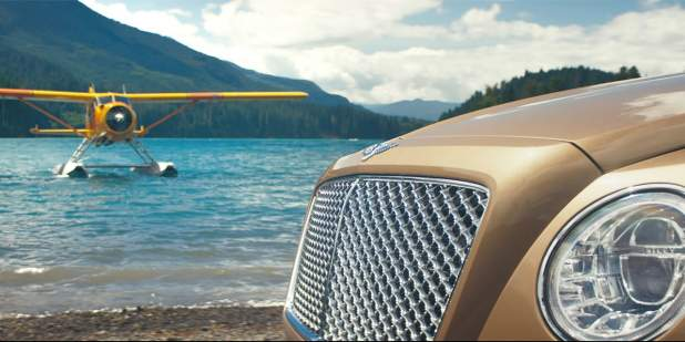 Bronze Bentley Bentayga parked lakeside with a seaplane hovering on water | Bentley Motors