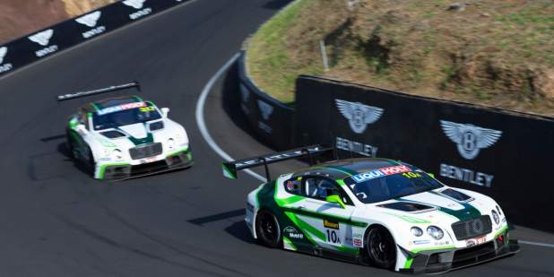 Two Bentley Continental GT3 race cars on a race track with Bentley background banners | Bentley Motors