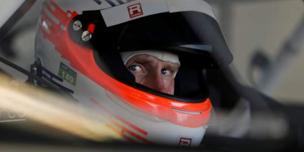 Headshot of Chris Dyson wearing a racing helmet looking toward the camera at Miller Motorsports Park in Utah | Bentley Motors
