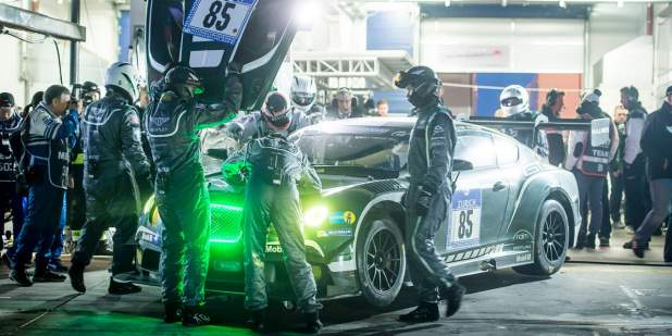 Engineers working on an emerald green Bentley Continental GT3 with green illuminated grille | Bentley Motors