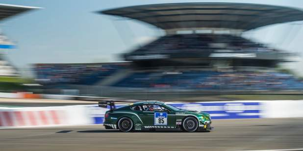 Side view of an emerald green Bentley Continental GT3 at Nürburgring race track | Bentley Motors