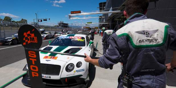 A Bentley Continental GT3 parked a pit stop surrounded by Bentley engineers | Bentley Motors
