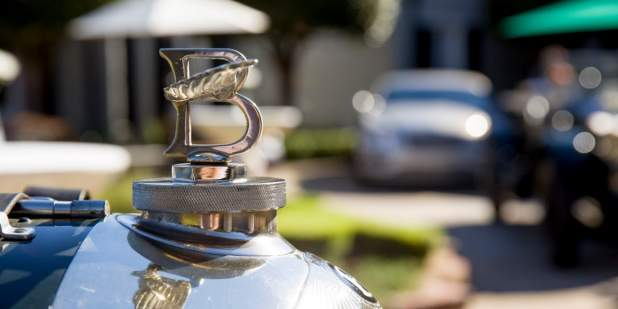 Up-close shot of early Bentley emblem in front of a luxurious location| Bentley Motors